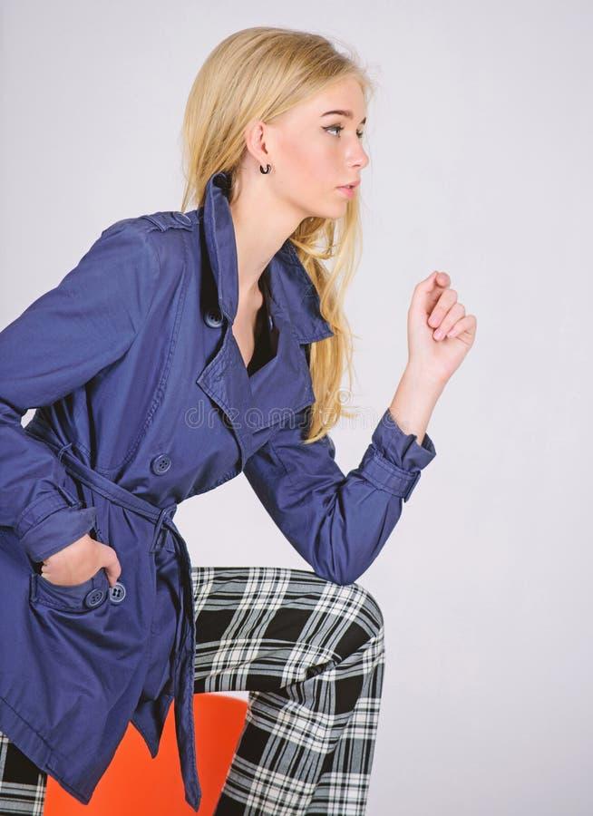 M?ste ha begrepp Kvinnamakeupframsida som poserar laget p? modern stol Trendigt lag Kl?der och tillbeh?r Blandande stilar arkivfoto