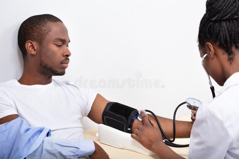 M?tande blodtryck f?r doktor av t?lmodign fotografering för bildbyråer