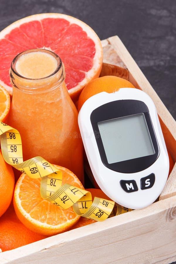 M?tre de glucose pour le niveau de mesure de sucre, coctail fra?chement m?lang? d'agrume et centim?tre Diab?te, amincissant et sa photo stock