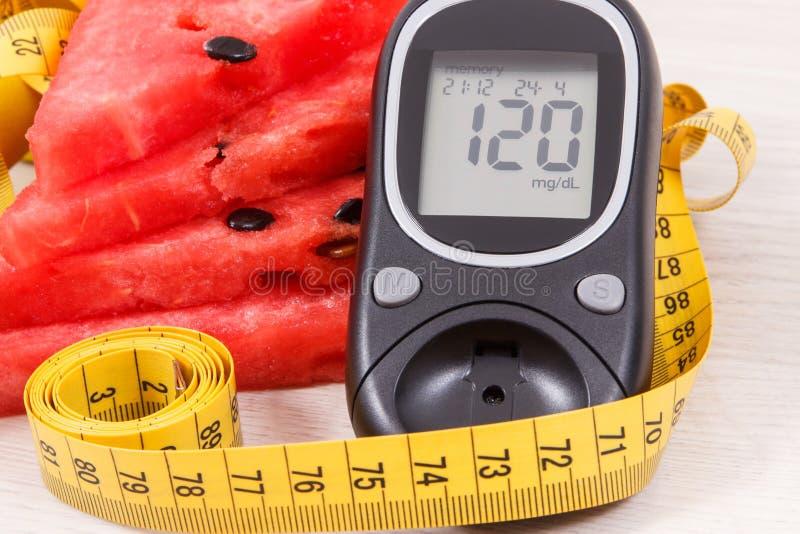 M?tre de glucose pour le niveau de mesure de sucre, past?que contenant des minerais et le ruban m?trique, diab?te et concept sain photographie stock