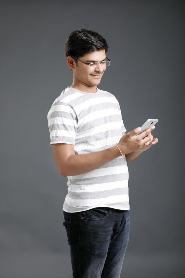 M?vil indio joven de la tenencia del hombre a disposici?n imagen de archivo libre de regalías