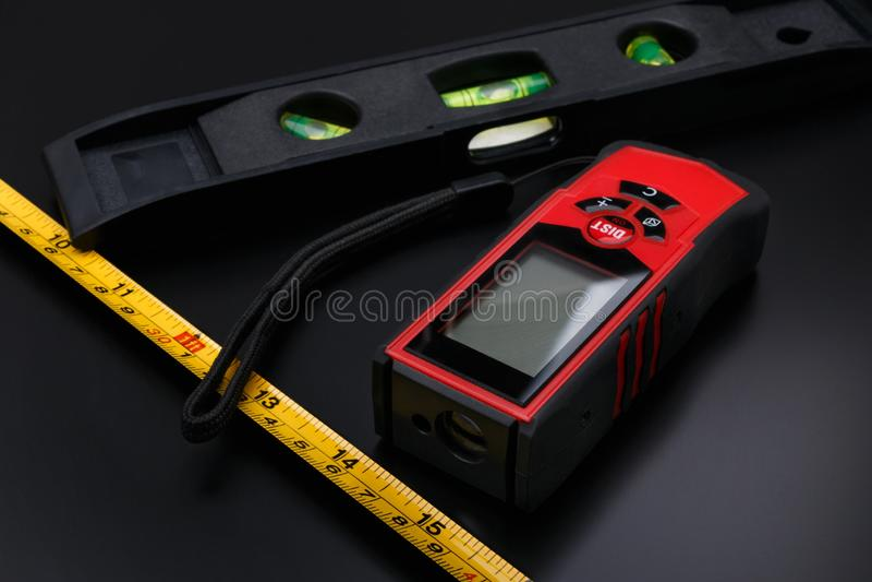 Maßband, Laser-Band und auf schwarzer Mattoberfläche gerade errichten lizenzfreies stockbild
