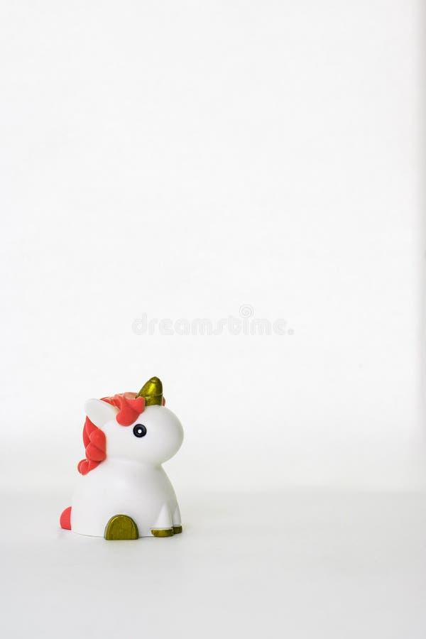 Mała śliczna biała jednorożec zabawka z koralowym włosy na białym pustym tle odosobniony kosmos kopii symbol dzieciak colour pion fotografia stock