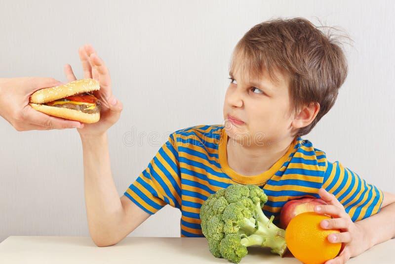 Mała śliczna chłopiec w pasiastej koszula przy stołem odmawia hamburger na rzecz zdrowej diety na białym tle zdjęcia stock