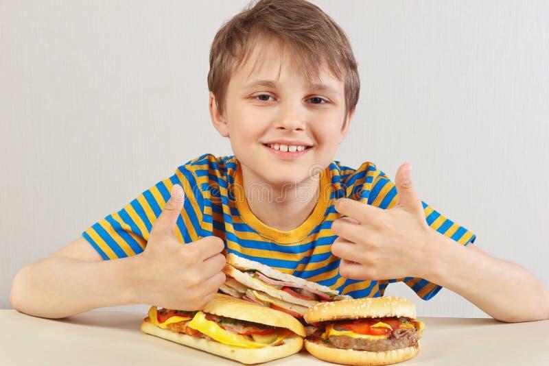 Mała śmieszna chłopiec w pasiastej koszula przy stołem poleca hamburgery i kanapkę na białym tle fotografia stock