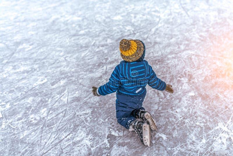 Mała chłopiec 2-3 lat, jest ubranym spódnicę, spadał na lodzie jego łyżwy Pojęcie pierwszy lekcja łyżwiarstwa poparcie, niepowodz fotografia royalty free