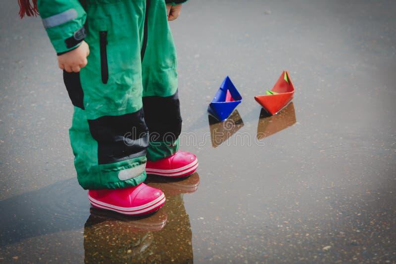 Mała dziewczynka bawić się z papierowymi łodziami w wodnej kałuży zdjęcie stock