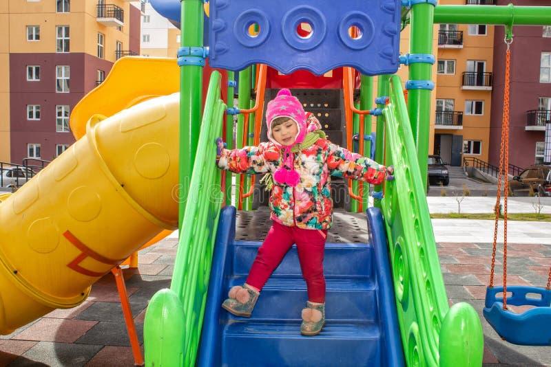 Mała dziewczynka, ciepło ubierająca, w kurtce i kapeluszu bawić się na boisku z obruszeniami i huśtawkami w podwórzu residentia zdjęcia stock