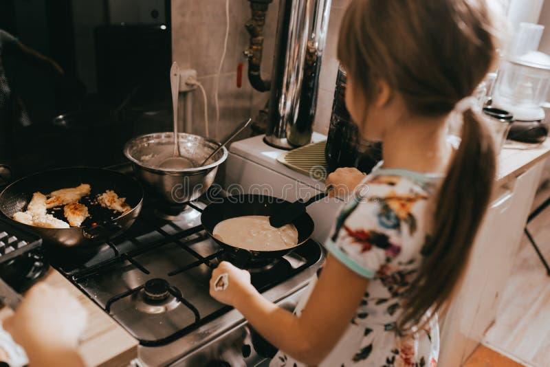 Mała dziewczynka pomaga jej macierzystym kulinarnym blinom dla śniadania w małej wygodnej kuchni obrazy stock