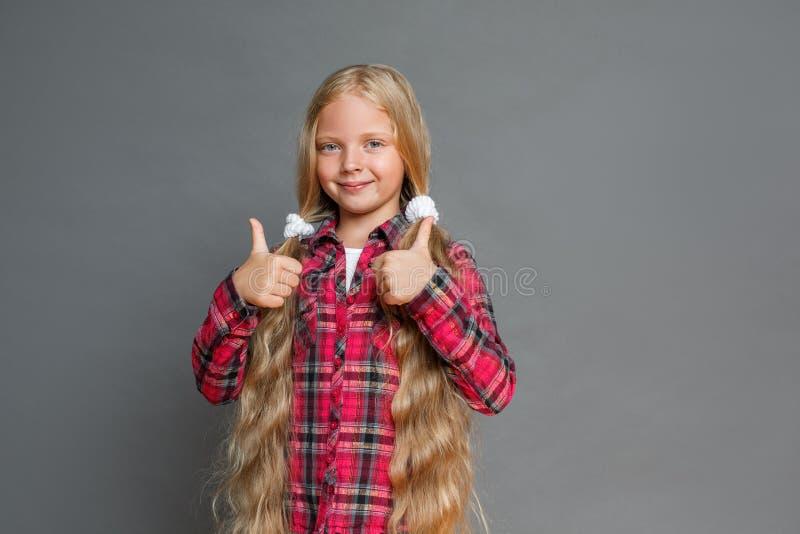 Mała dziewczynka stoi odizolowywająca na popielatych pokazuje aprobatach patrzeje kamerę radosną z ponytails obrazy stock