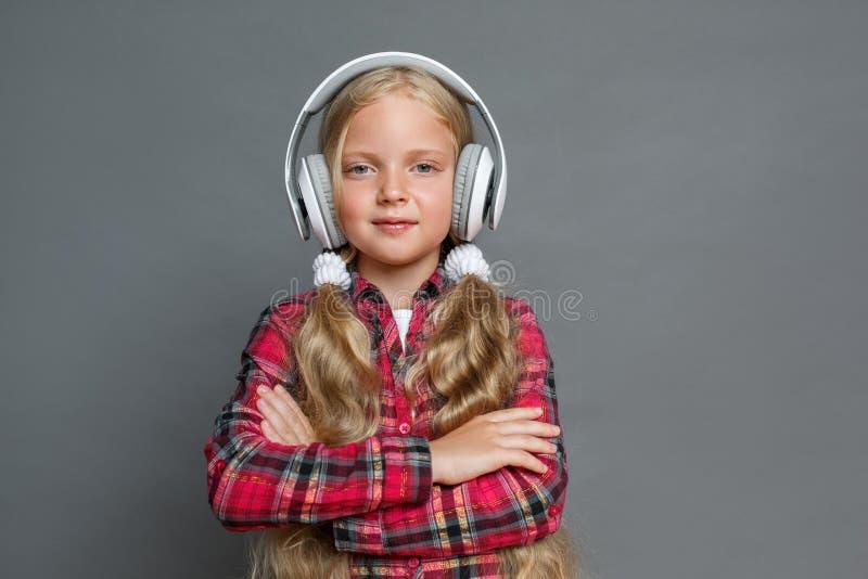 Mała dziewczynka stoi patrzeje kamerę ufną w hełmofonach odizolowywających na popielatych krzyżować rękach z ponytails obrazy stock