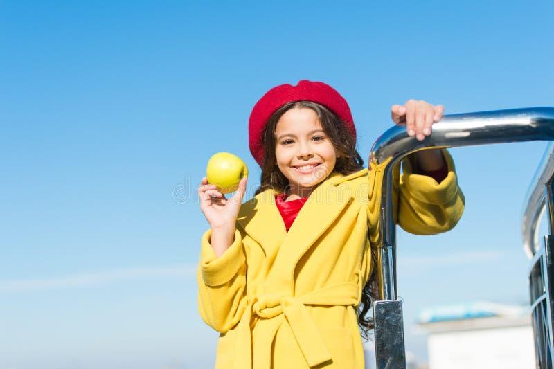 Mała dziewczynka trzyma organicznie zielonego jabłka szczęśliwy dziecko z oraganic owoc na słonecznym dniu Mały dziecko cieszy si obrazy royalty free