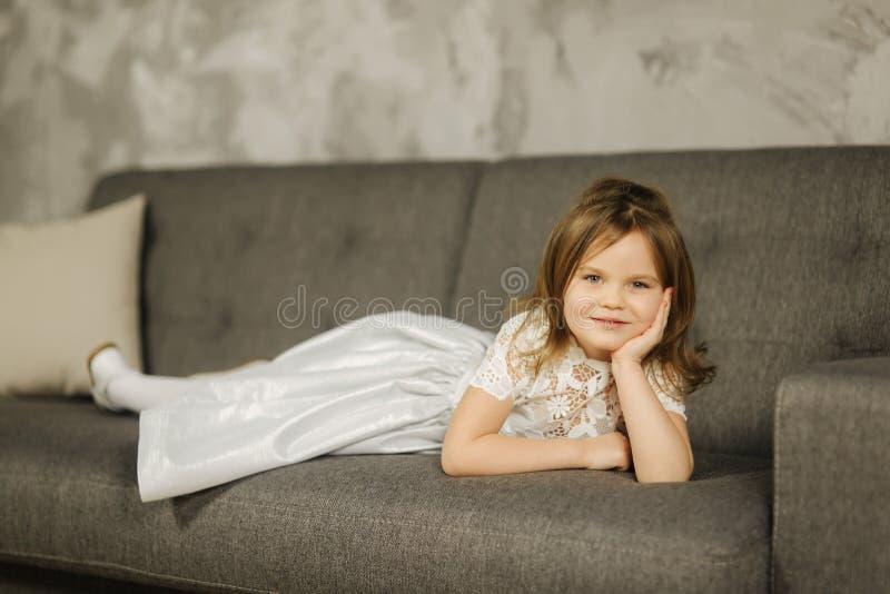 Mała dziewczynka w biel sukni na kanapie Pięcioletnia dziewczyna w domu obraz stock