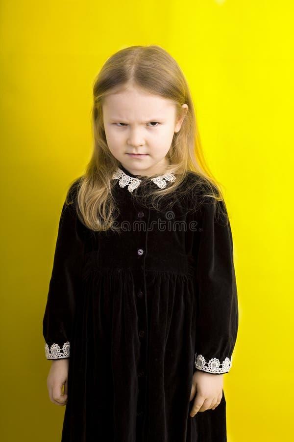Mała dziewczynka w czarnej sukni na żółtym tle emocje złość spójrz zła obrazy royalty free