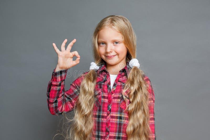Mała dziewczynka z ponytails stać odizolowywam na popielatego seansu ok przyglądającej kamerze satysfakcjonował obraz stock