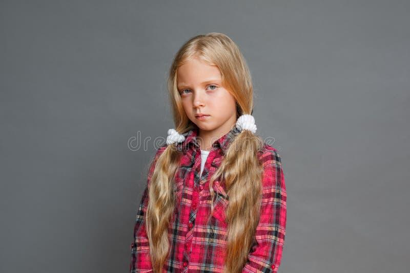 Mała dziewczynka z ponytails stać odizolowywam na popielaty nieszezególnym obrazy royalty free