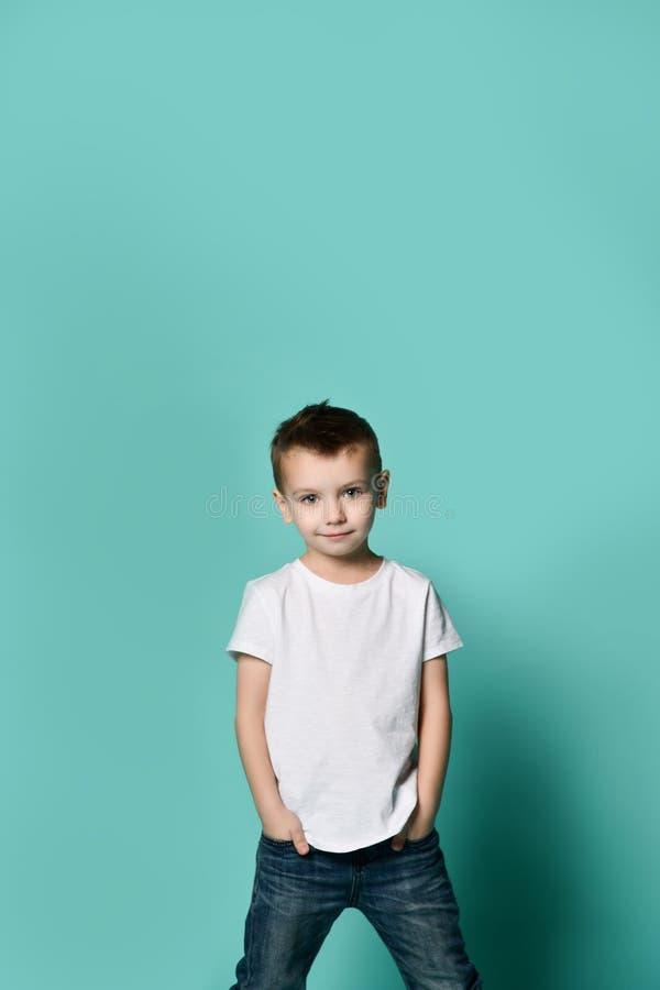 Mała modna chłopiec pozuje przed błękit ścianą fotografia stock