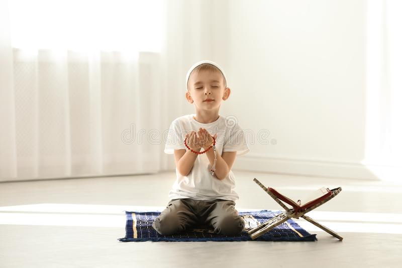 Mała Muzułmańska chłopiec z misbaha i Koran modlenie na dywaniku obrazy royalty free