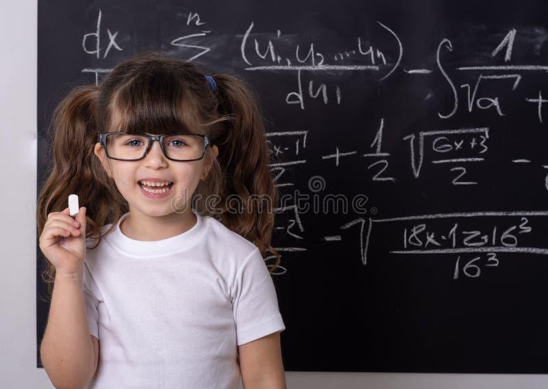 Mała szkolna dziewczyna w sali lekcyjnej Genialny dzieciak fotografia royalty free