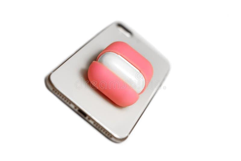 Małe białe słuchawki z ładowarki pudełkiem w jaskrawym menchii pokrywy pudełku, telefon komórkowy, wybierająca ostrość, dinamic w fotografia stock
