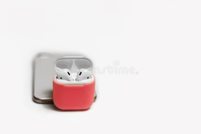 Małe białe słuchawki z ładowarki pudełkiem w jaskrawym menchii pokrywy pudełku, telefon komórkowy, wybierająca ostrość zdjęcie royalty free