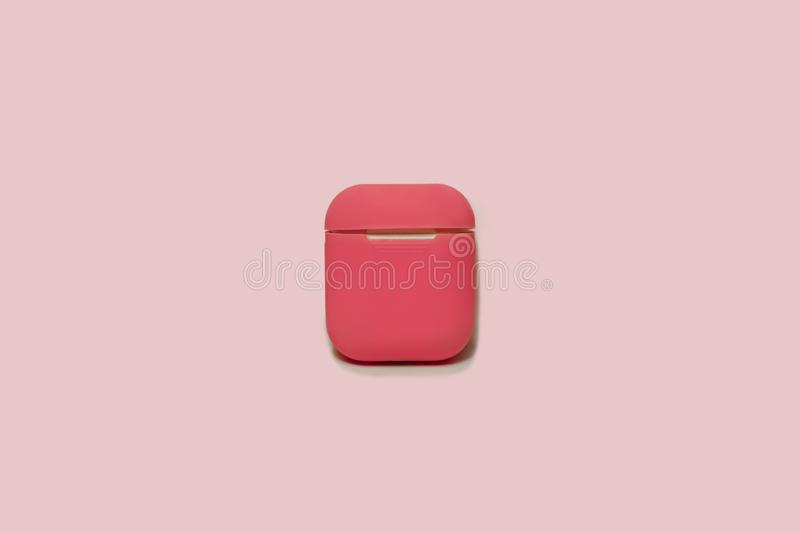 Małe białe słuchawki z ładowarki pudełkiem w jaskrawym menchii pokrywy pudełku, wybierająca ostrość zdjęcia stock