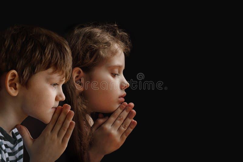 Małe dziecko składał jego rękę z modleniem w czarnym tle zdjęcia royalty free