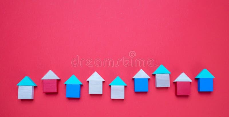Mały drewniany bloku dom modeluje z dachami na czerwonym tle obraz royalty free