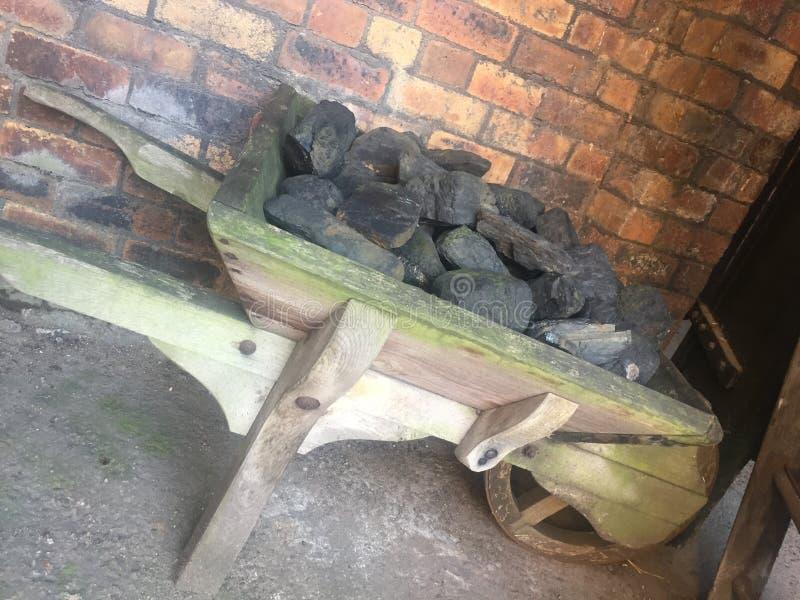 Mały drewniany wheelbarrow wypełniający z węglem obraz royalty free