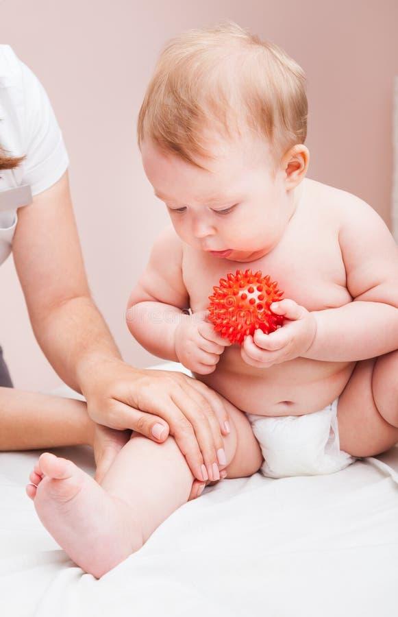 Mały dziecko otrzymywa osteopathic traktowanie jej noga w pediatrycznej klinice zdjęcia stock