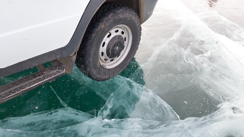 Mały koło stary samochód i część samochodowa pozycja na jasnym lodzie jeziorny Baikal w surowych mrozie z wycieczki samochodowej zdjęcie stock