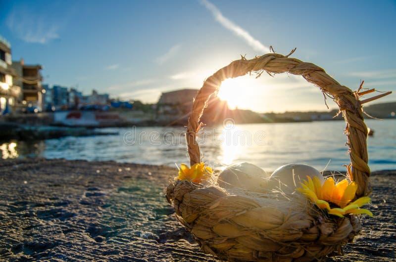 Mały kosz z dwa Easter jajkami na morzu doc na złotej godzinie obrazy stock