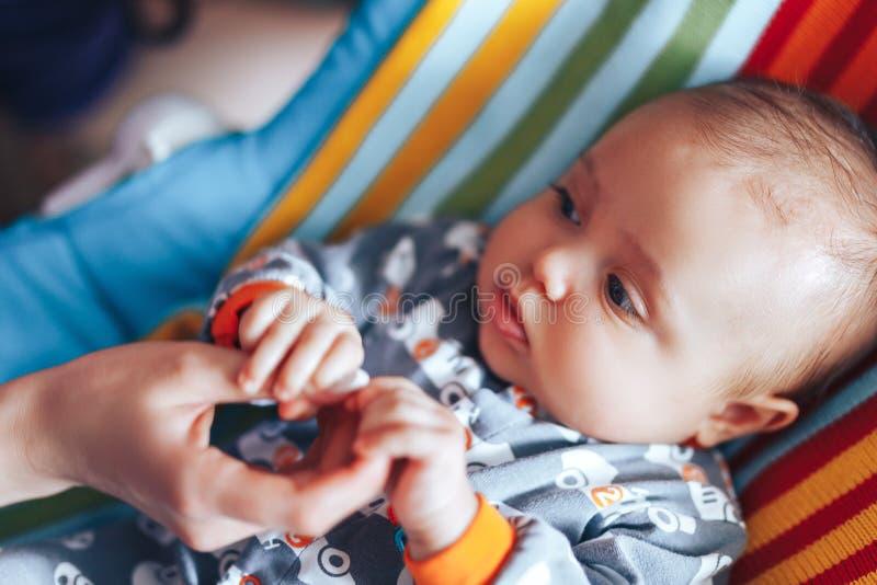 Mały nowonarodzony dziecka mienia parent& x27; s jeden ręka w górę makro- strzału, fotografia stock