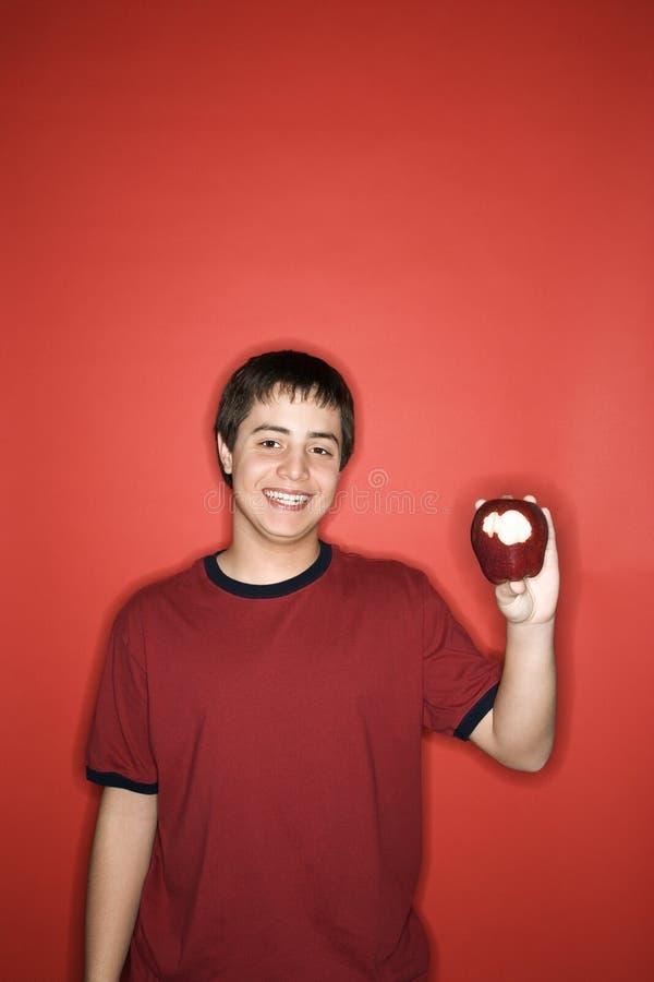 Maçã adolescente caucasiano da terra arrendada do menino. foto de stock