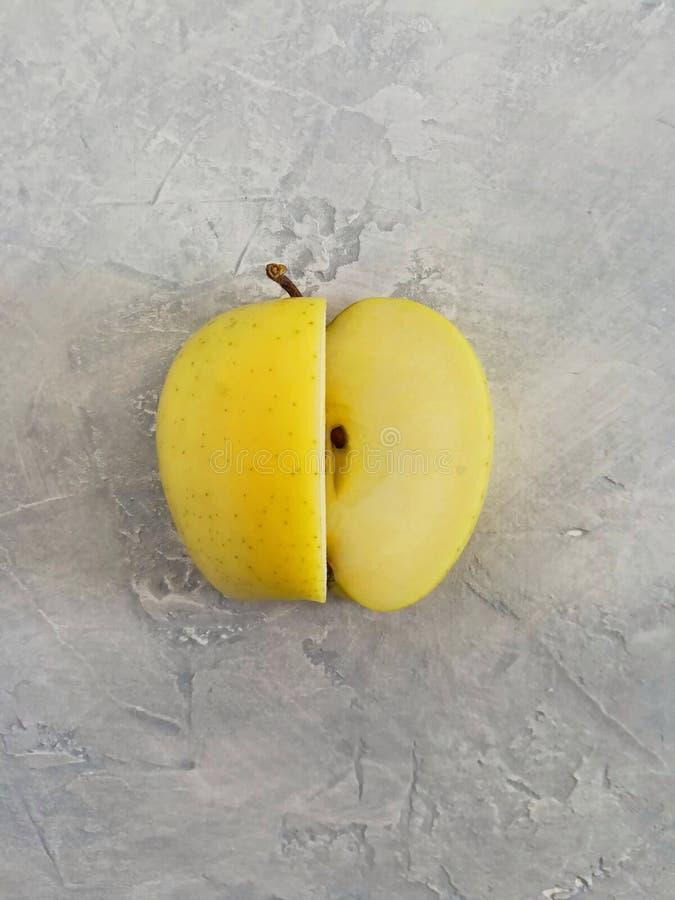 Maçã amarela madura em um fundo concreto cinzento imagens de stock