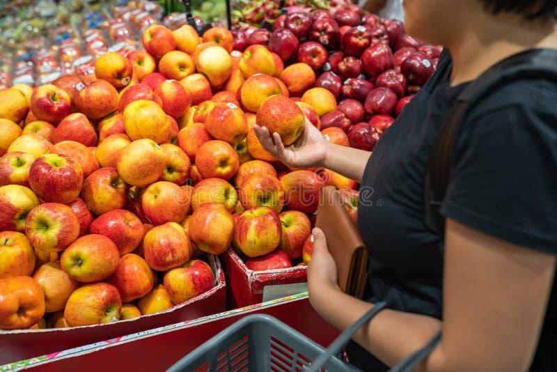 Maçã asiática da colheita da mulher no suporte de fruto no supermercado imagens de stock