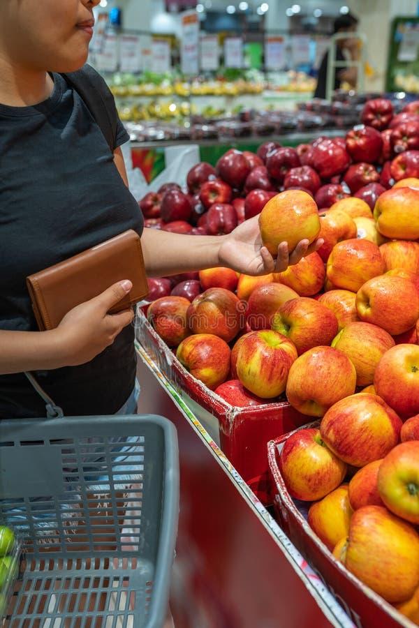 Maçã asiática da compra da mulher no suporte de fruto no supermercado fotografia de stock