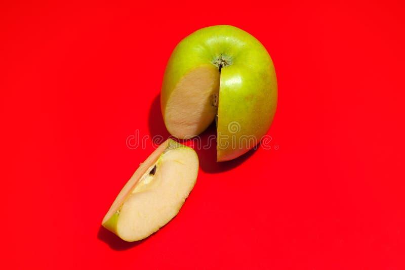 Ma?? cortada verde madura isolada em um fundo vermelho Conceito comendo e de dieta saud?vel fotografia de stock royalty free