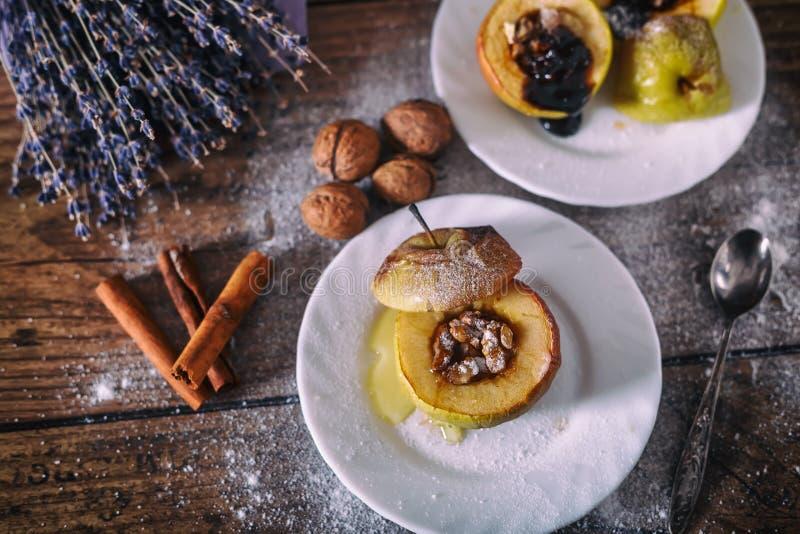 Maçã cozida enchida com porcas, mel e chocolate nas placas de sobremesa brancas, fundo de madeira escuro Doce do Natal Eatin saud fotografia de stock