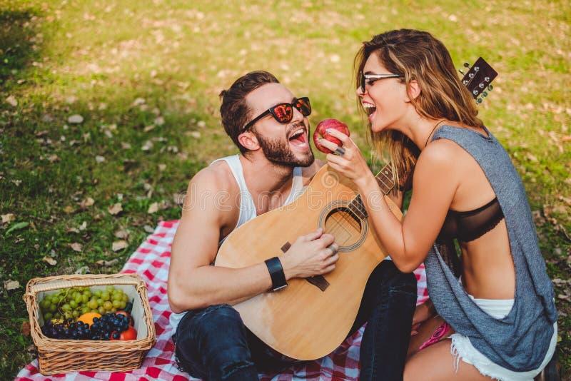 Maçã de alimentação da menina a seu noivo em um piquenique fotografia de stock