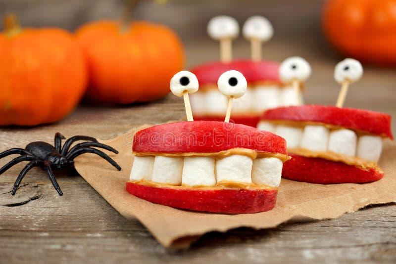 Maçã de Dia das Bruxas, marshmallow, dentes do monstro da manteiga de amendoim sobre a madeira foto de stock