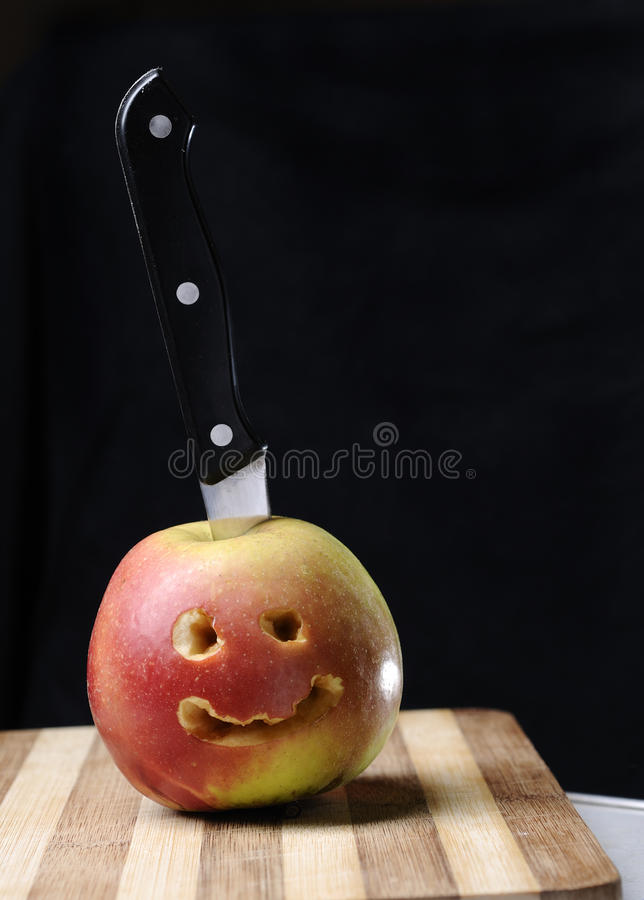 Maçã de sorriso penitrated com uma faca imagem de stock royalty free
