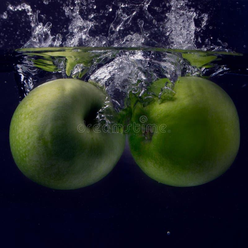 Maçã dois verde sob a água com uma fuga de bolhas transparentes imagem de stock