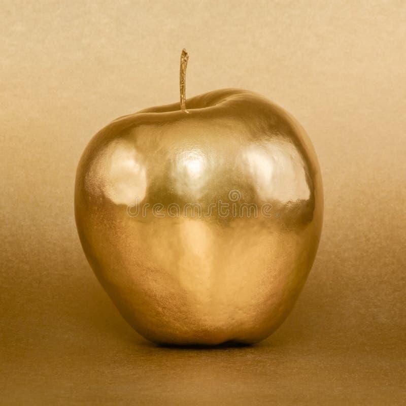 Maçã dourada no fundo do ouro imagem de stock royalty free