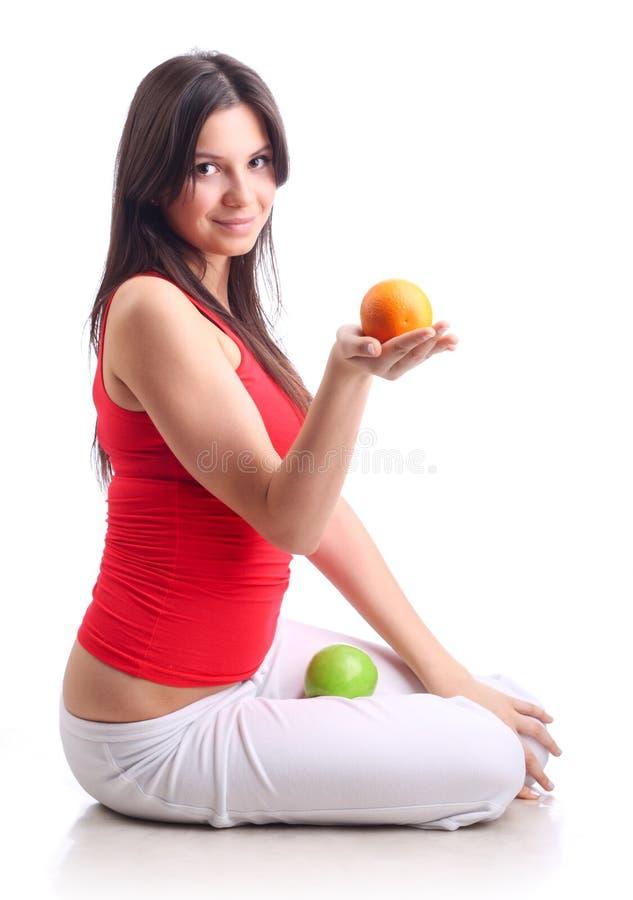 Maçã e laranja da preensão da rapariga. Isolado imagem de stock royalty free