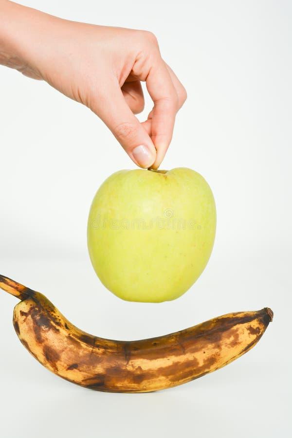 Maçã fresca contra a banana mofado imagem de stock royalty free