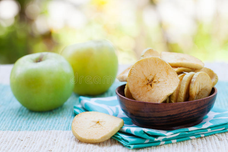 A maçã fritada desidratada secada lasca-se em uma bacia de madeira com espaço fresco da cópia da maçã foto de stock royalty free