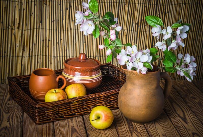 Maçã madura e ramo de florescência de uma Apple-árvore em um frasco da argila fotos de stock