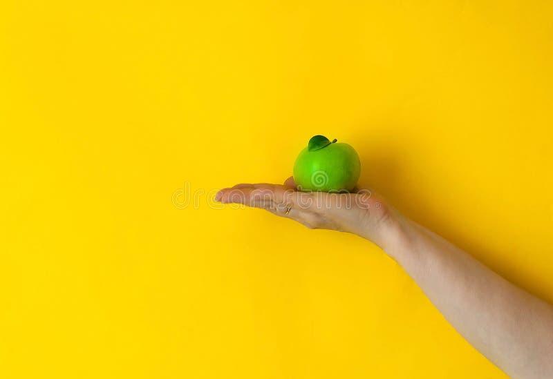 A maçã verde é mantida pela mão fêmea no fundo amarelo, luz natural, espaço da cópia fotografia de stock