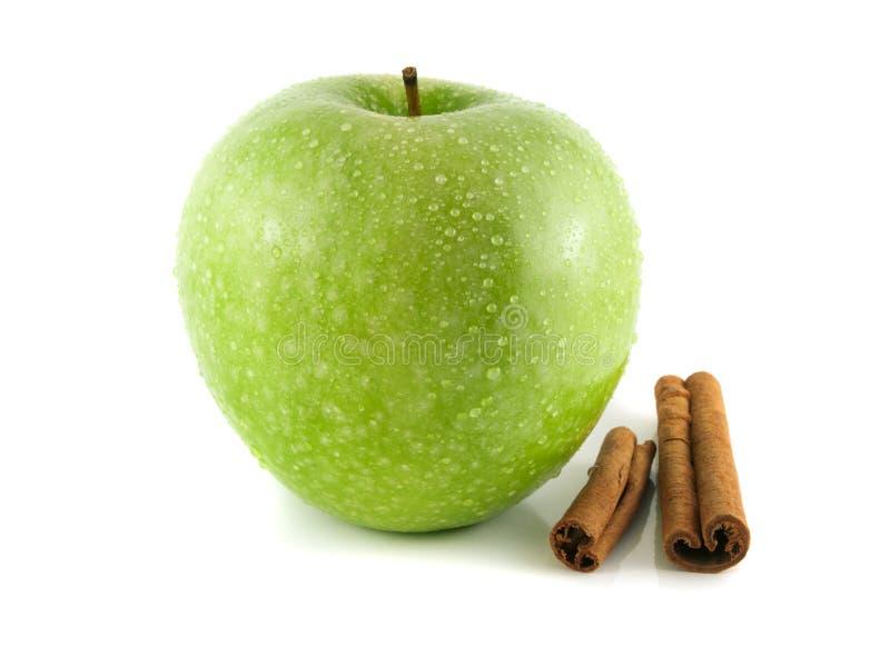 maçã verde com as vagens da canela no branco fotografia de stock royalty free